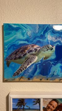A beautiful sea turtle swims through the oceanic colors of a paint pour.